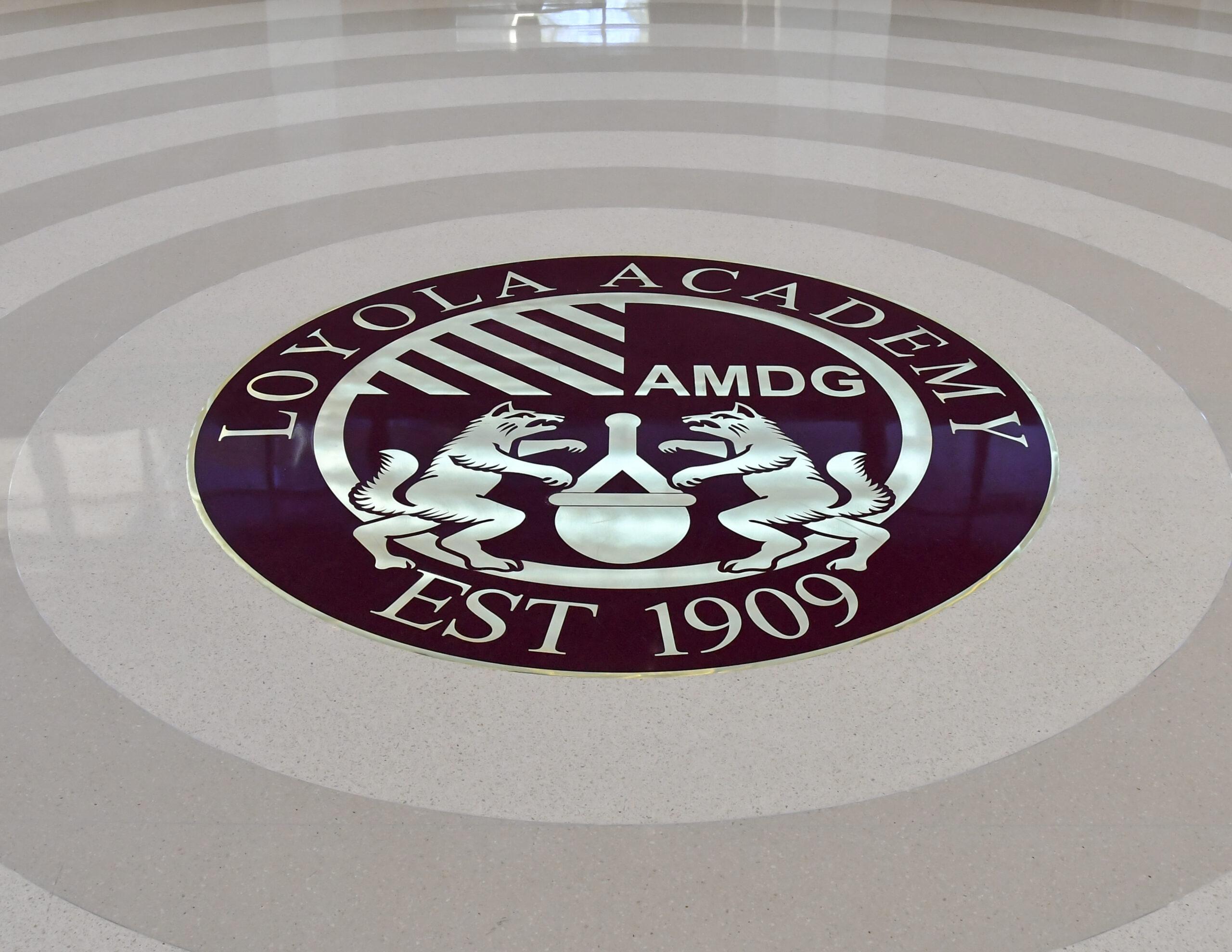 Signage and school emblem on floor, Loyola Academy Aquatic Center.